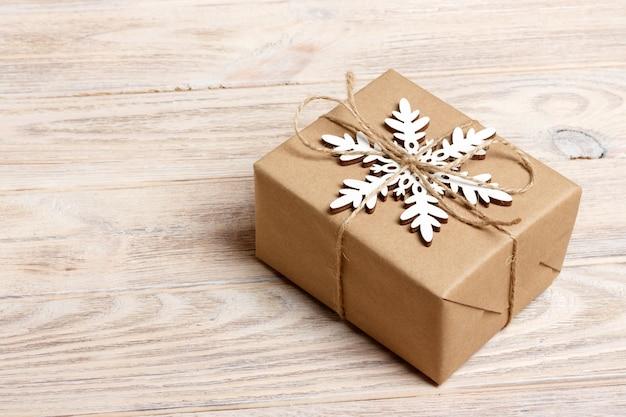 白い木製の背景平面図にクラフト紙と白い雪片で飾られたクリスマス手作りギフトボックス。冬のクリスマスの休日のテーマ。明けましておめでとうございます。メリークリスマスのグリーティングカード