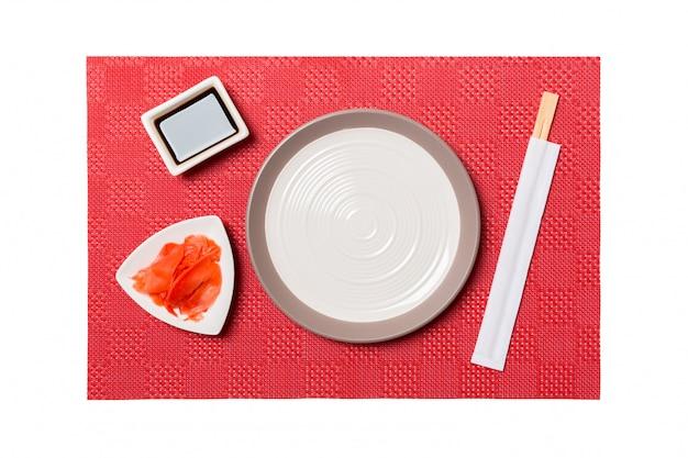 Пустая круглая белая тарелка с палочками для суши и соевым соусом, имбирь на красных матовых суши. вид сверху