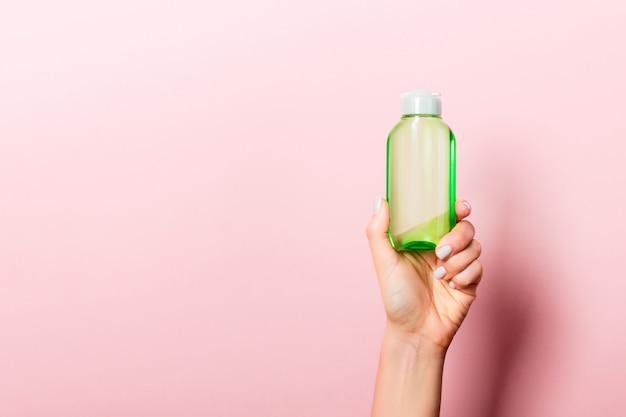 分離されたローションのクリームボトルを持っている女性の手。女の子はピンクの背景にチューブ化粧品を与える