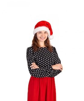 Портрет красивой усмехаясь сексуальной девушки в платье, эмоциональной девушки в шляпе рождества санта клауса изолированной на белизне,