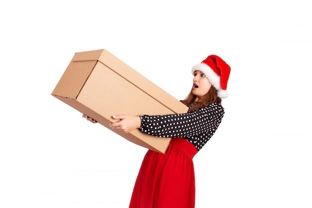 Портрет возбужденной удивленной девушки в платье, держащем большую и тяжелую подарочную коробку, изолирован на белом,