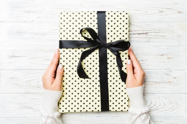 白い素朴な木製、クリスマスコンセプトまたは他の休日手作りプレゼントボックス、コンセプトトップビューに色のリボンとストライプギフトボックスを保持している女性の手