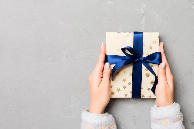 ギフトを保持している女性の手のフラットレイアウトラップし、灰色のセメント木製、クリスマスに弓で飾られたと
