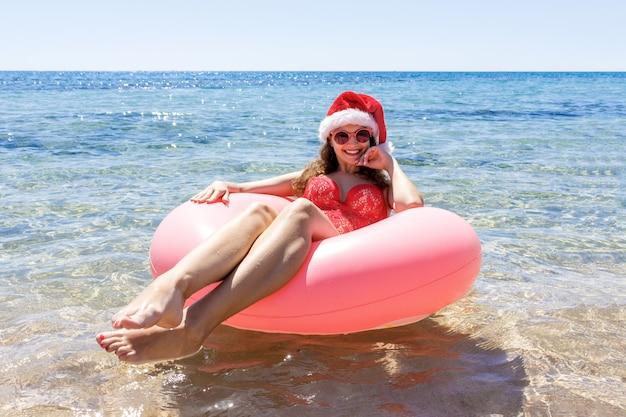 青い海でリラックスしたピンクのサークルとクリスマス帽子の美しい若い女性