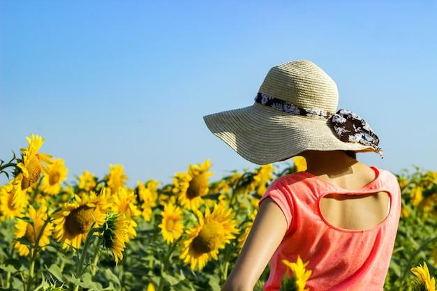 ヒマワリの分野で麦わら帽子の流行に敏感な女性。旅行の女の子は、ひまわり畑で夏の夕日を楽しむ