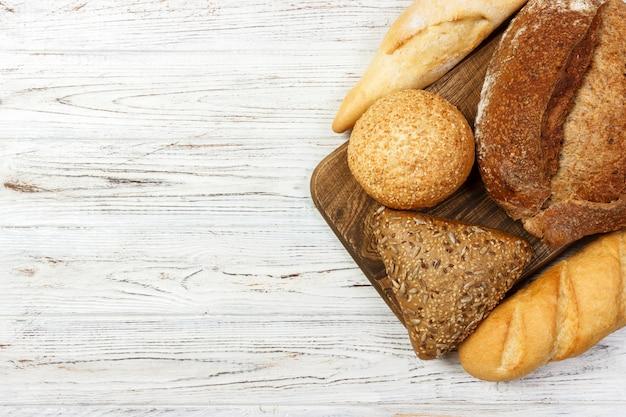 白い木製の背景に焼きたてのパンの品揃え。コピースペース平面図