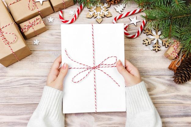 女の子は、子供のクリスマスの手紙、ギフトボックスとクリスマスの装飾のクリスマスの手紙を保持しています。