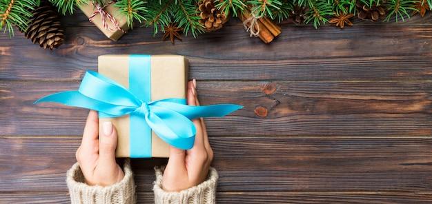 暗い木製のテーブル、クリスマスの準備の概念、バナーギフト包装にリサイクル紙で手作りプレゼントボックスを保持している女性の手