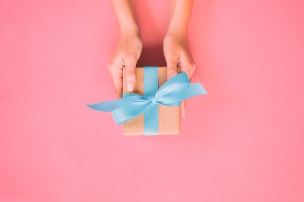 女性の手は、包まれたバレンタインやその他の休日の手作りのプレゼントを紙に青いリボンで与えます。