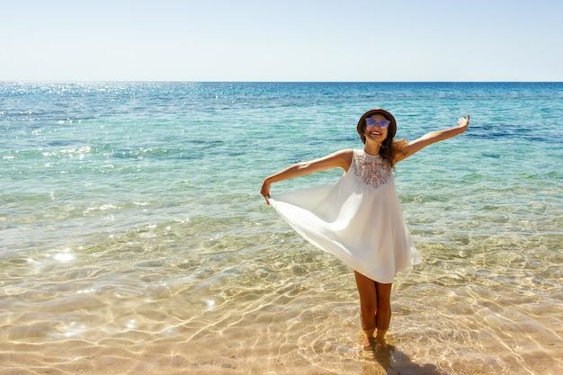 Молодая женщина в белом платье и шляпа стоя на пляже и наслаждаясь солнцем