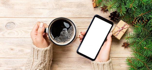 モスクとモダンなスマートフォンを保持している女性の手とクリスマスデコレーションと木製のテーブルの上のコーヒーのマグカップ