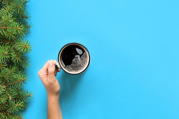 青のコーヒーのマグカップを持つミニマルなスタイルの女性手