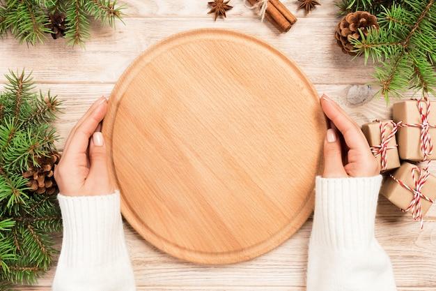 女性の手は、クリスマスの装飾が施された木製のテーブルに空のラウンドまな板を保持します。