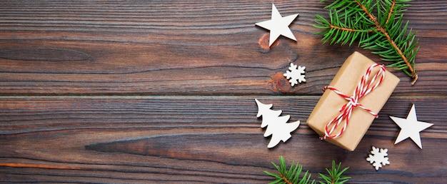Подарочная коробка рождества обернутая в рециркулированной бумаге, с взгляд сверху ленты с космосом экземпляра на предпосылке знамени деревенской.