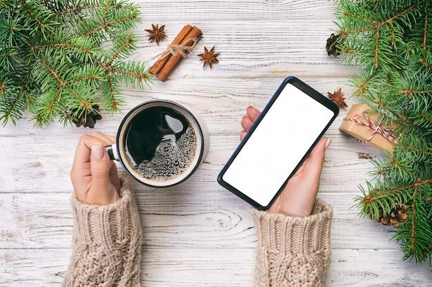スマートフォンとコーヒーのクリスマスの装飾のトップビュー