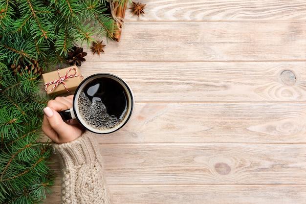素朴な木製のテーブルにホットコーヒーのカップを保持している女性
