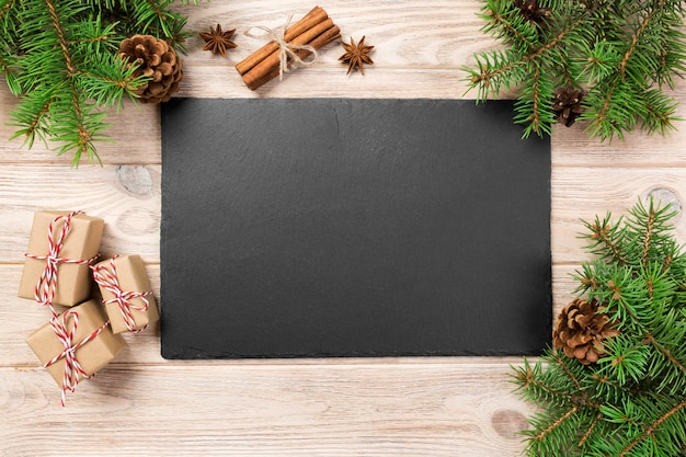 クリスマスの装飾と木製のテーブルの上のスレート石皿。木製の表面に黒いスレート石。