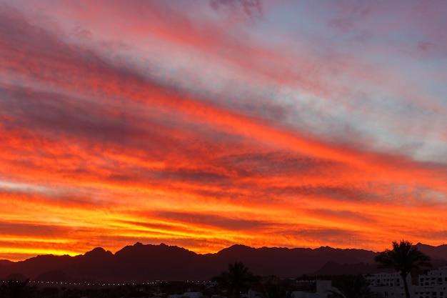 Красочный оранжевый закат над горными холмами