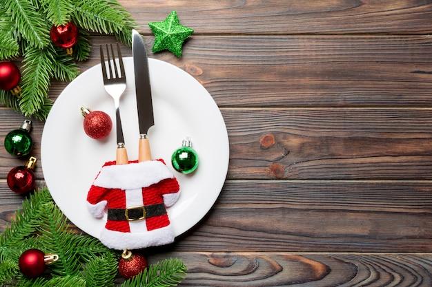 フォーク、ナイフ、木製の表面にモミの木とクリスマスデコラトインに囲まれたプレートのトップビュー