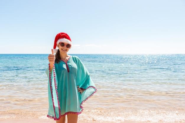 楽園のビーチでリラックスしたサンタ帽子の休日女性