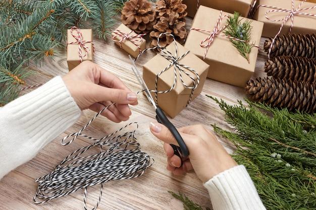 木製のテーブルに贈り物を包む手。