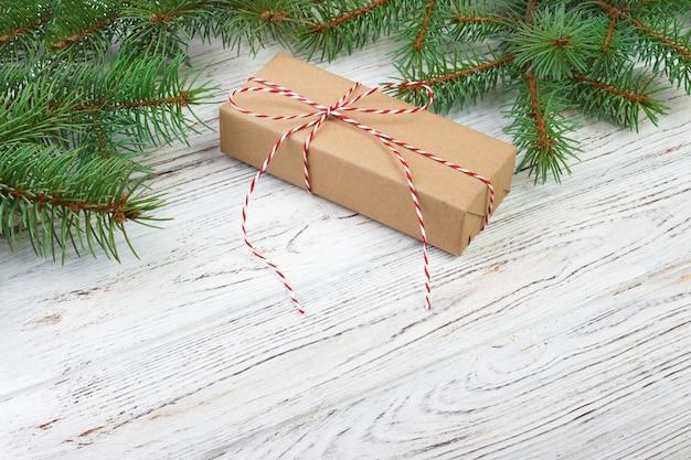 木製の表面トップビューにモミの枝とギフトボックス