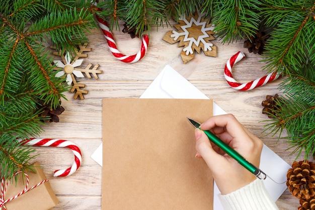 Человек, пишущий рождественские письма на крафт-бумаге с украшениями на деревянной поверхности