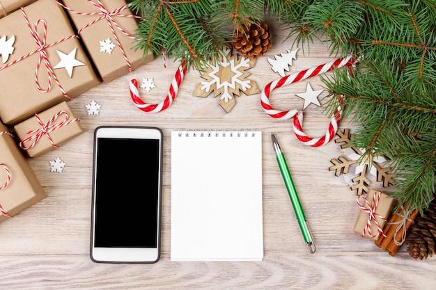 ギフトボックス、携帯電話、空白のノートブックでクリスマスの装飾