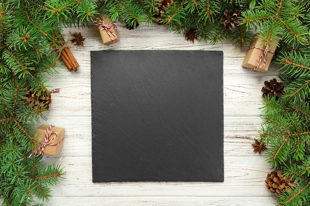 上面図。木製のクリスマス背景に空の黒いスレートの正方形板。新年の装飾が施された休日のディナー料理