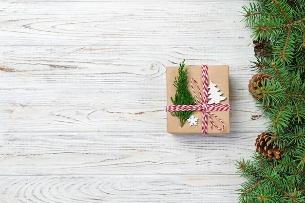 Рождественская подарочная коробка, завернутые в переработанную бумагу, с лентой лук, с лентой на деревенском фоне. день отдыха