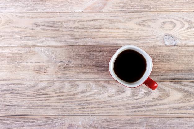 木製のビンテージテーブルの上の赤カップでコーヒーのトップビュー