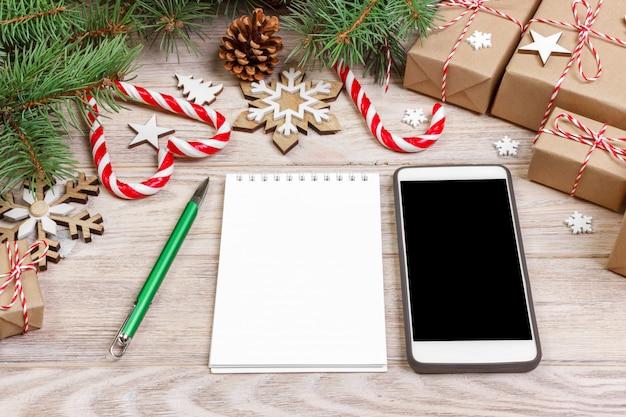 クリスマスの時期、白い背景の上のクリスマスの装飾、フラットレイアウトトップビューのノートブックスマートフォンブランド