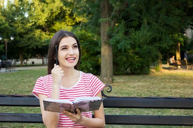 Сногсшибательная девушка на скамейке думает с книгой и ручкой у ее головы в парке