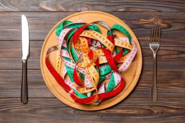 木製の丸皿のスパゲッティの代わりにカラフルな測定テープ