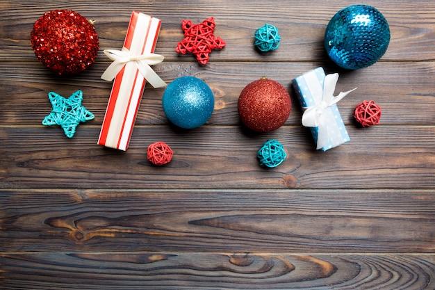 Елочный шар, подарок и креативные украшения на деревянном фоне