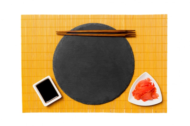 Пустая круглая черная тарелка с палочками для еды