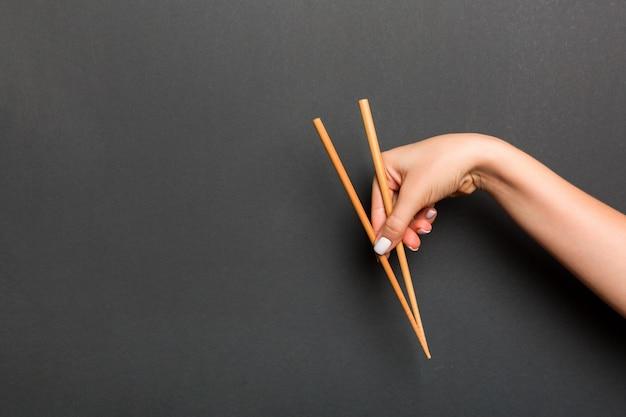 女性の手で保持されている木製の箸