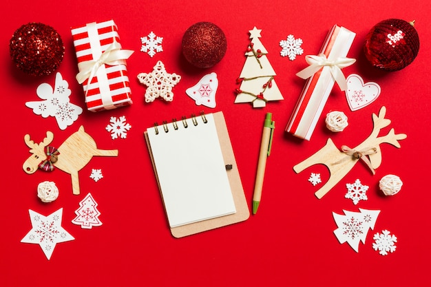クリスマスの装飾で作られた赤い背景の上のノートブックのトップビュー