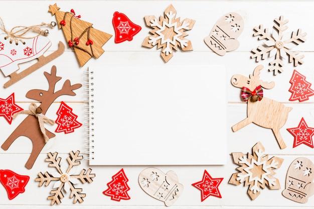 クリスマスの装飾で作られた木製の背景上のノートブックのトップビュー
