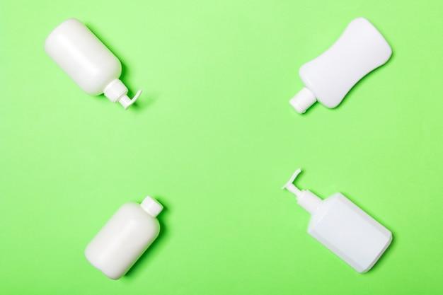 Набор белых косметических контейнеров, изолированных на зеленом фоне