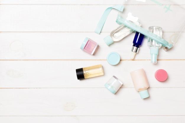 白い木製の背景に旅行サイズの化粧品ボトルのセット