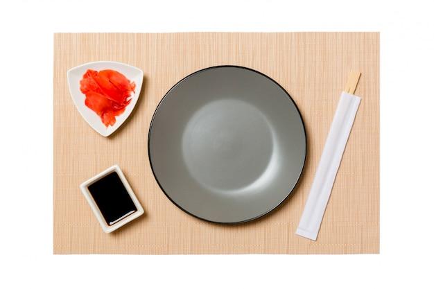 Пустая круглая серая тарелка с палочками для суши и соевым соусом