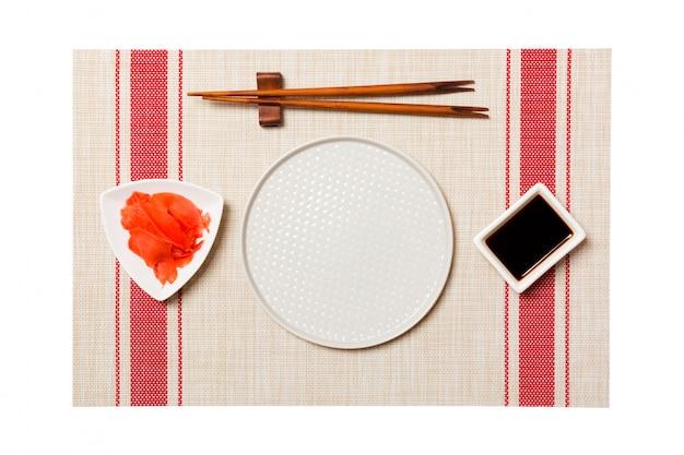 寿司と醤油の箸で空の白い丸皿