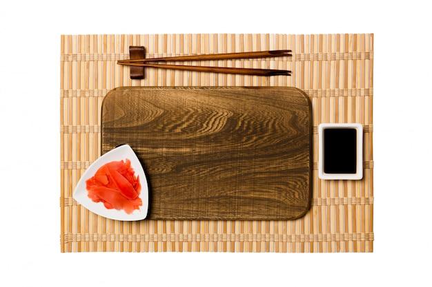 Пустая прямоугольная коричневая деревянная тарелка с палочками для суши