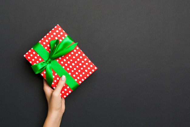 Женщина руки, держа подарочной коробке на цветном фоне