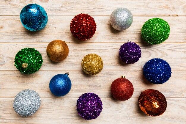 木製の背景にカラフルなクリスマスボールのトップビュー