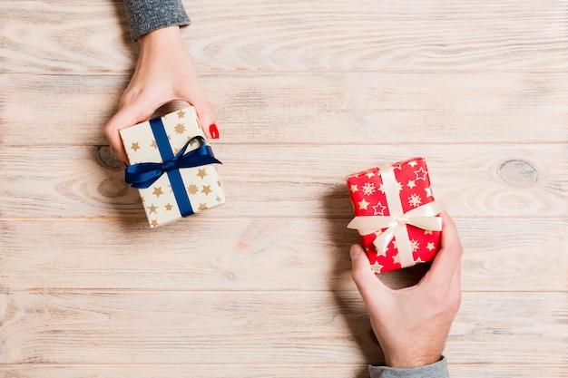 木製の背景に贈り物を交換する男女の平面図