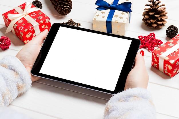 木製のクリスマス背景にタブレットを保持している女性の手の上から見る