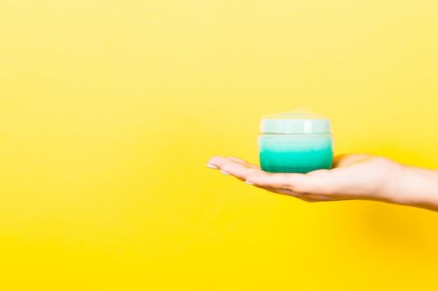 分離されたローションのクリームボトルを持っている女性の手。女の子は黄色の背景に瓶化粧品を与える