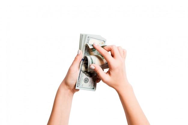 女性の手でお金の束の平面図。分離された白のドルを数えるイメージ